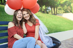 The bride with his girlfriend sitting in the park. Keep balloons Stock Photos
