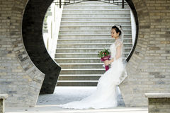 Bride hold bridal bouquet with white wedding dress near a brick arch. Wear white crown on her head, black hair, sweet smile, happy. red lip, flower shape Stock Image