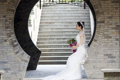 Bride hold bridal bouquet with white wedding dress near a brick arch. Wear white crown on her head, black hair, sweet smile, happy. red lip, flower shape Royalty Free Stock Image