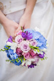 Bride hold colored blue-pink wedding bouquet. Wedding bouquet is holding by bride. Background white wedding dress Royalty Free Stock Images