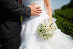 Bride hold groom by the hand and wedding bouquet. Focus on weddi Royalty Free Stock Images