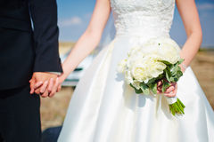 Bride hold groom by the hand and wedding bouquet. Focus on weddi Stock Photography