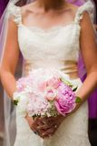 Bride holding a beautiful bouquet of flowers Stock Photos