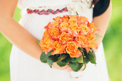 A bride holding a beautiful bouquet of orange roses Stock Photo