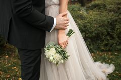The bride is holding a beautiful bouquet of white roses and green leaves. Embrace the newlyweds, the hands of the bride and groom royalty free stock photos
