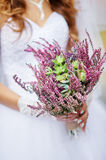 Bride holding a beautiful wedding bouquet of wild flowers.  Stock Image