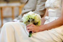 Bride holding beautiful wedding flowers. On her knees Stock Photography