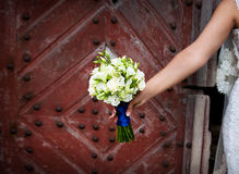 Bride holding beautiful wedding flowers bouquet. On old wooden background Stock Images