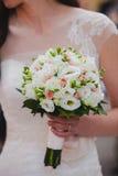 Bride holding beautiful white wedding bouquet. Outdoor Stock Photo