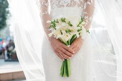 Bride holding beautiful white wedding flowers bouquet. Wedding day Stock Photos