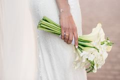 Bride holding beautiful white wedding flowers bouquet. Wedding day Royalty Free Stock Photo