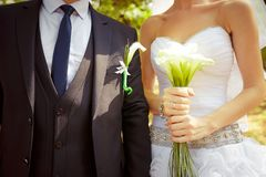 Bride holding beautiful white wedding flowers bouquet. Groom standing behind with same flowers in boutonniere Royalty Free Stock Photos