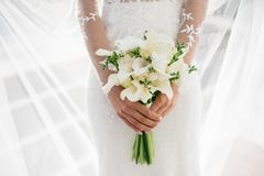 Bride holding beautiful white wedding flowers bouquet. Wedding day Stock Images