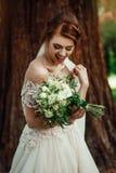 Nice white wedding bouquet in bride`s hand. Bride holding big wedding bouquet on wedding ceremony Stock Photo
