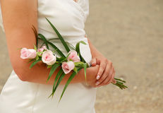 Bride holding boquet. Close up of bride's arms holding boquet of pink roses royalty free stock photography