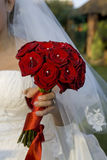 Bride holding a bouqet. Of red roses royalty free stock photos
