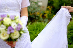 Bride holding bouquet. A detailed view of a bride's weeding dress and flowers bouquet Royalty Free Stock Photography