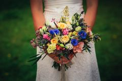 Bride is holding a bouquet on the background of greenery Stock Photography