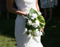 Bride holding a bouquet of flowers. Bride in a white wedding dress holding a beautiful bouquet of flowers Stock Images