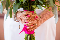 Bride Holding Bouquet of Flowers. Bride with henna tattoos holding her bouquet of flowers on her wedding day royalty free stock photo