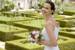 Bride Holding Bouquet In Formal Garden Stock Photo