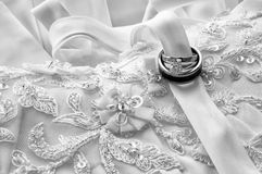 The Wedding Rings. Bride and Grooms wedding rings on the wedding gown wrapped in ribbon Royalty Free Stock Photo