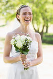 Bride holding bouquet while laughing in garden Royalty Free Stock Photos