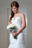 Bride holding bouquet and looking down Royalty Free Stock Images