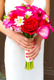 Bride Holding Bouquet of Mixed Flowers. Before the wedding ceremony a bride is holding her bouquet of mixed flowers Royalty Free Stock Images