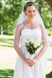 Bride holding bouquet in park Royalty Free Stock Images
