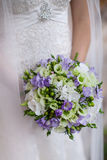 The bride holding a bouquet. Photo of the bride in a white dress with a bouquet in hands without a face royalty free stock image