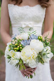 The bride holding a bouquet. Photo of the bride in a white dress with a bouquet in hands without a face royalty free stock photos