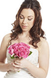Bride holding a bouquet of pink roses thoughtful Royalty Free Stock Photography