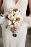 Bride holding bouquet of roses with feathers Stock Photo