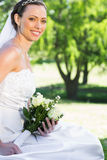 Bride holding bouquet while sitting in garden Royalty Free Stock Image