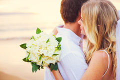 Bride holding bouquet of white flowers gazing at the ocean into Stock Images