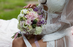 Bride holding bridal bouquet on her knees. Stock Images