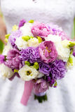 Bride holding bridal bouquet with white, pink and purple flowers Royalty Free Stock Photo