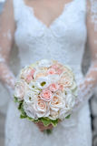 Bride holding buquet. Beautiful bride holding wedding bouquet made of pink and white roses stock images