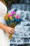 Bride holding wedding bouquet in front of a waterfall Royalty Free Stock Photo
