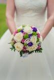 Bride holding colour wedding bouquet of flowers Stock Photos