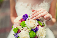 Bride holding colour wedding bouquet of flowers with ladybug on Stock Image