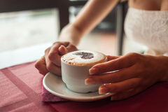 Bride holding cup of coffee. In cafe Stock Photography