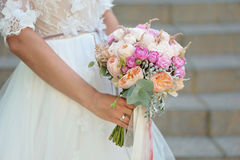 Bride holding delicate marriage bouquet Stock Images