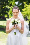 Bride holding flower bouquet in garden Royalty Free Stock Photos