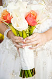 Bride holding flower bouquet. Hands of bride in traditional white wedding dress holding bouquet of flowers Royalty Free Stock Photography
