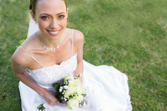 Bride holding flower bouquet while sitting in garden Stock Images