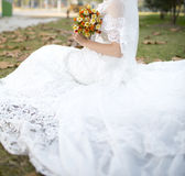 Bride holding flower in grass Stock Photo