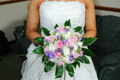 Bride holding flowers. And showing dress detail on wedding day Stock Images