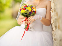 Bride Holding Flowers with Red Ribbon Royalty Free Stock Image